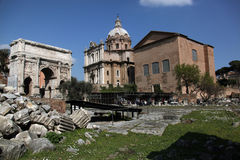 Part of the ancient Forum in Rome. Arch of Septimius Severus and the building of the Senate in the ancient Roman Forum of Rome stock image
