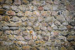 Part of ancient stone wall for background or texture. Beautiful old grey stone wall background with moss and darken edges. Stock Photo