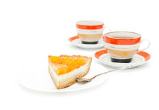 Part of apricot cake and two cups Royalty Free Stock Image