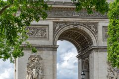 Part of the arc de triomphe in paris france. With tree in front of the building, summer time Royalty Free Stock Photos