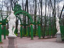 Part of arched lattices with sculptures in the park of the Summe. A group of sculptures and part of arched lattices of the main avenue in the Summer Garden park Royalty Free Stock Photo