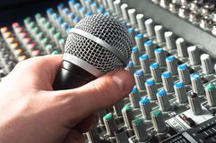 Part of an audio sound mixer. With microphone in hand stock photos
