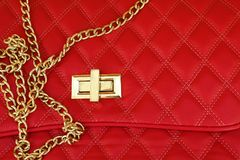 Part of a bag of red leather with a fastener and chain stock image
