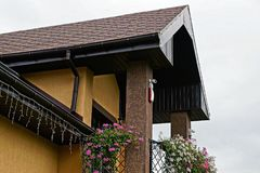 Part of the balcony with flowers and a tiled roof against the sky Royalty Free Stock Photos