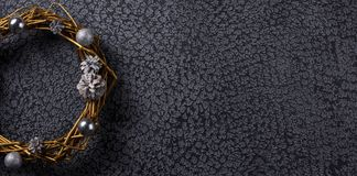 Part of a beautiful Christmas wreath painted in gold on a black background. The decor of the interior. Banner. Part of a beautiful Christmas wreath painted in stock photography