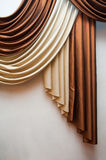Part of beautifully draped curtain and wall with patterns Stock Image