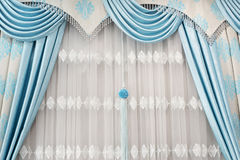 Part of beautifully draped curtain on the window in the room. Close up of curtain drapery with pendants. Luxury curtain, home deco. R. Turquoise and blue panels Royalty Free Stock Image