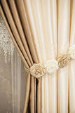Part of beautifully draped curtain on the window in the room. Floral tieback. Close up of piled curtain. Beige and brown luxury cu Stock Image