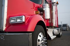 Part of big rig bonnet American semi truck standing on parking l. Bright red big rig classic American semi truck with chrome parts and flat bed semi trailer royalty free stock photography