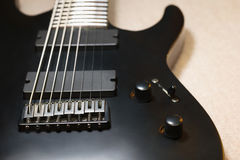 Part of black eight string electro guitar. Closeup Stock Images