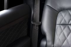 Part of black  leather car seat detail with focus on safety belt locks. Modern luxury car interior Royalty Free Stock Images