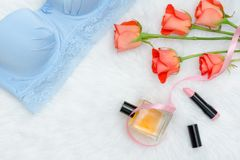Part of blue bodice with lace on white fur, orange roses. Lipsti. Ck and parfums. Fashionable concept Stock Photo