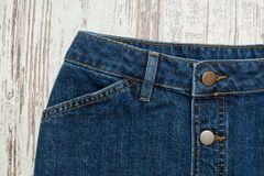 Part of the blue denim skirt. Wooden background, fashionable con. Cept Stock Photo