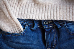 Part of blue jeans and woolen pullover close up. Selective focus Stock Photography