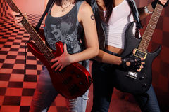 Part of bodies of two women playing electric guitar. In studio with checkered background in red light and smoke Stock Photos