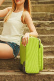 Part body of female tourist with suitcase. Stock Photo