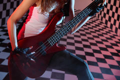 Part of body of girl playing electric guitar. Part of body of girl playing red electric guitar in studio with checkered background in smoke and pink light Stock Photography