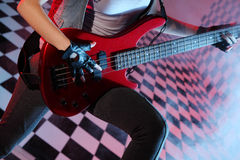 Part of body of woman playing electric guitar. In studio with checkered background in smoke and purple light Royalty Free Stock Photo