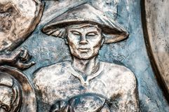 Part of monument with man in hat in Vietnam, Asia. Stock Photo