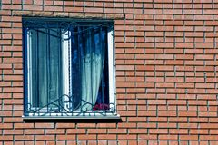 Window with a curtain behind a lattice on a brown brick wall Stock Photography