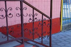 Part of the brown handrails with a forged pattern on the steps on the street near the wall stock image