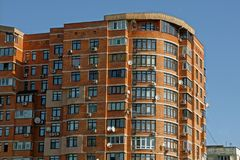 Brown multi-storey house with windows and balconies on the sky Stock Photo