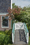 Part of brown house near the small white bridge with green trees around it. In the summer in the Netherlands Royalty Free Stock Images