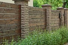 Part of a brown fence of wooden boards and bricks in green grass. Part of a brown long private fence of wooden boards and bricks in green grass stock photos