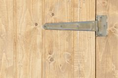 Part of the brown wooden door with hinges.  Stock Photo