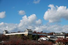 The part of building at Himeji Castle, Looking from out side with red autumn tree and blue sky background. stock photo