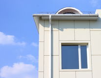 Part of a building wall with window and gutter against the blue cloudy sky Royalty Free Stock Image