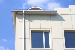 Part of a building wall with window and gutter against the blue sky Royalty Free Stock Images