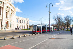 Part of Burgtheater, red tram and people walking, Vienna Stock Image