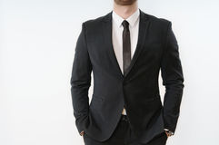 Part of business man body in black suit with hands in pockets on stock image