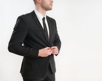 Part of business man body side button up his black suit on white. Background; business concept Stock Image