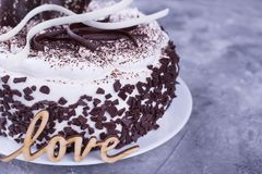 Part of cake, love word. Cake and inscription on gray background. Sweet gift for the holiday Stock Photography