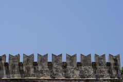 Part of castle sky blue. Part of castle with crenellation. Rhodes Town in Greece Stock Photos