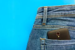 Part of cellphone in blue jeans back pocket stock photos