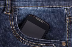 Part of cellphone in the pocket of blue jeans Stock Image