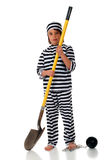 Part of the Chain Gang. Sweating, unhappy elementary child in prison garb carrying a shovel.  A heavy ball is chained to her foot Royalty Free Stock Image