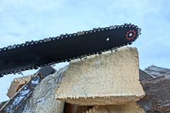 Part of a chainsaw with a black tire and a chain on a wooden board. In the street royalty free stock photo