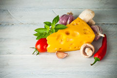 Part cheese with vegetables and basil on wooden board Royalty Free Stock Image
