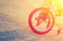 Part of the children's bicycles and child on the background of t Royalty Free Stock Images