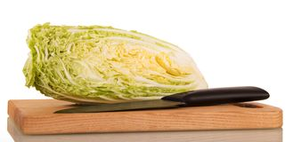 Part of Chinese cabbage, wooden board and knife isolated on whit royalty free stock photo