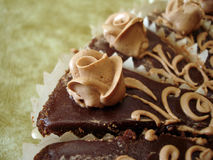 Part of chocolate cake. With flowers on textured background Royalty Free Stock Photos