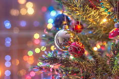 Part of Christmas tree, with colorful glass balls, small decorations and colorful light reflections Royalty Free Stock Photography