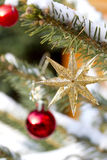 Part of a Christmas tree with ornaments. Part of a Christmas tree with red and golden ornaments Royalty Free Stock Image