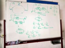 White board with schematic drawing and formulas of an electric circuit. Physics class. royalty free stock photography