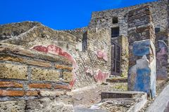 Part of the colored brick wall and street in Pompeii, Naples, Italy. The ruins of the ancient city, excavations of Pompei scavi. royalty free stock photography