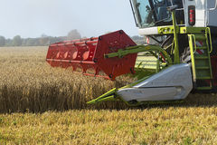 Part of a combine harvester working on a wheat field Stock Photography